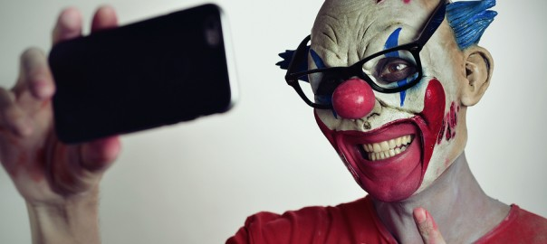 portrait of a scary evil clown taking a selfie with his smartpho